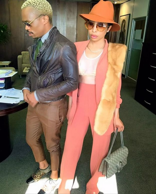 Khanyi's pant suit, sheer lacy top and fur scarf worn with Mui Mui sunglasses, a burnt orange hat and a Louis Vuitton bag.  Somizi's leather biker jacket, brown ¾ pants, green tie, blue shirt and animal print shoes. – What a colourful and stylish combination.