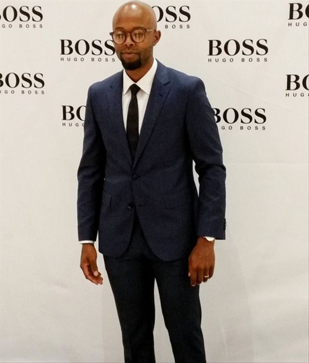 Snap back and tattoos? No honey, good job and great suits! Actor, Thapelo Mokoena suits up and suits it well. This time we check out his dark navy tailored suit that he wore to the launch of the Hugo Boss store at Mall of Africa recently. Brothers, you can never go wrong in a tailored suit with a crisp white shirt.