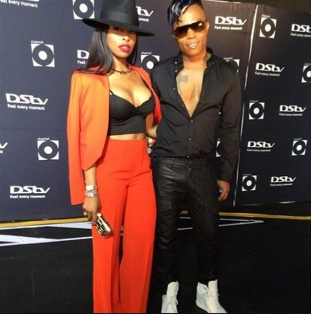 Khanyi's burnt orange jacket over her shoulders and a black bodice crop top is the perfect match to Somizi's all black ensemble.