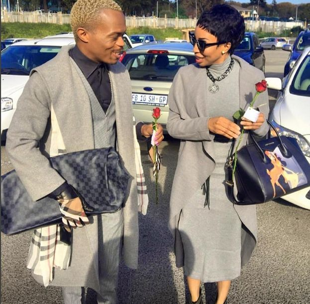 Khanyi's bodycon and grey loose woollen coat and statement bag matched perfectly with Somizi's Burberry gloves, grey coat, fitted grey suit and a black shirt. Elegance, style and class.