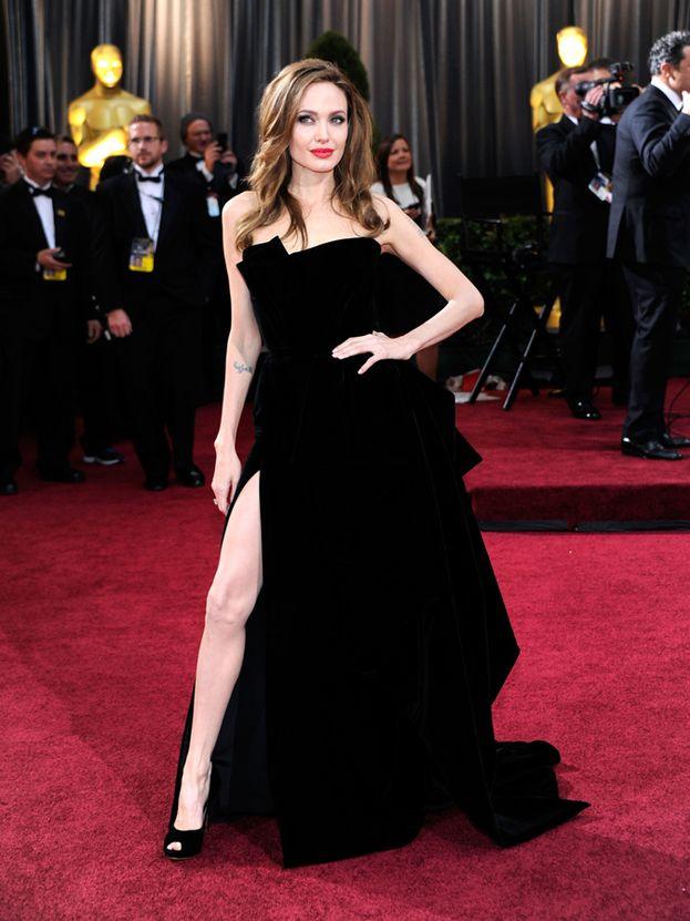 """La """"gamba fuori"""", mossa resa immortale da Angelina Jolie agli Oscar 2012. Notare il braccio opposto appoggiato sul fianco, che esalta l'effetto finale. Se hai gambe lunghe e snelle, è la tua."""