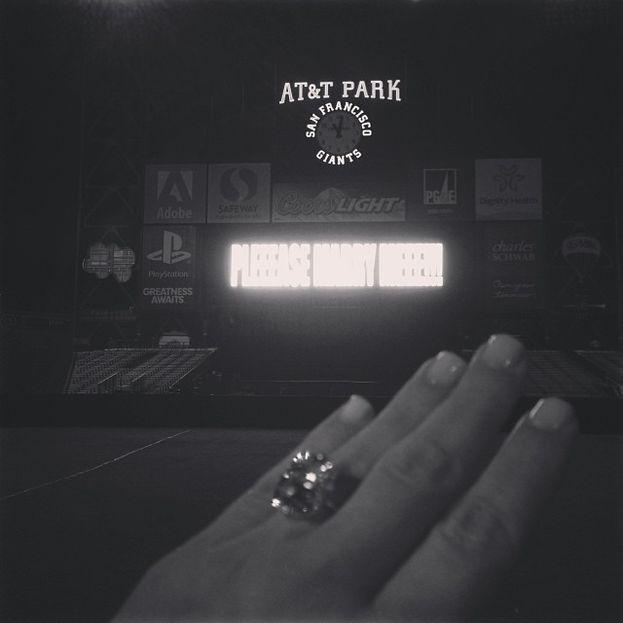 """La famosissima foto di Kim Kardashian che sfoggia il brillocco del fidanzamento con Kanye West. Notare la sobria scritta """"PLEEEASE MARRY MEEEE!!!' sul maxischermo dello stadio."""