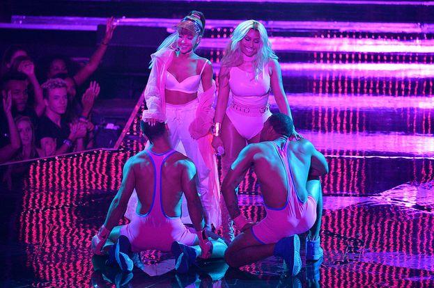Eccoci qua: Ariana e Nicki faccia a faccia (più o meno) con un paio di muscolosi ballerini in body rosa.